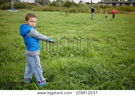 Boy stands holding control bar with attached flying cords of power kite on green meadow, view from back.