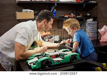 Father and little son build cars models on table in garage.