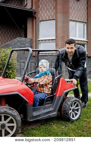 Smiling father pushes children car with little boy on driver seat in yard of brick cottage.