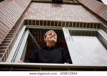 Smiling young man looks out from window of brick cottage, low angle view.