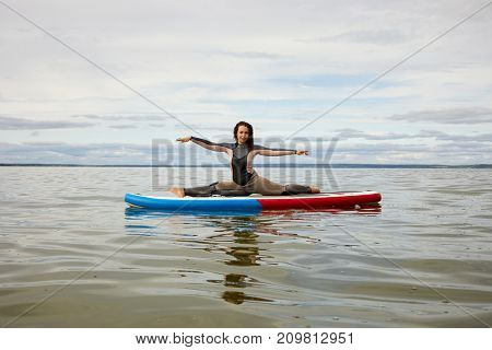 Young woman in surfer suit does split on inflatable SUP board on water.