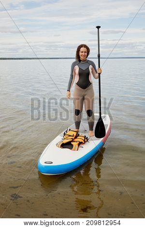 Woman in suit stands with paddle in hand on inflatable SUP board.