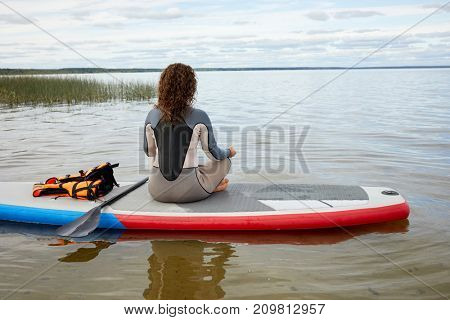 Woman in rashguard suit sits in yoga position on inflatable SUP board, rear view.