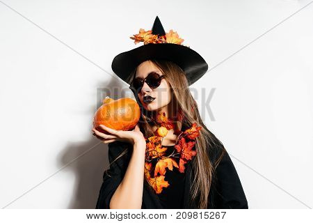 a girl in a witch's suit holds a small pumpkin