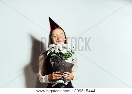 the girl in a festive cap smells a bouquet of flowers in her hands
