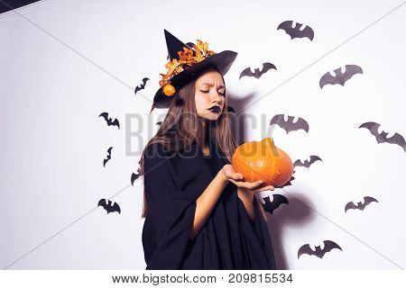 girl in a halloween costume holds a pumpkin in her hands