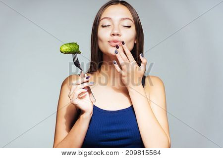 happy girl enjoying a salted cucumber on a white background