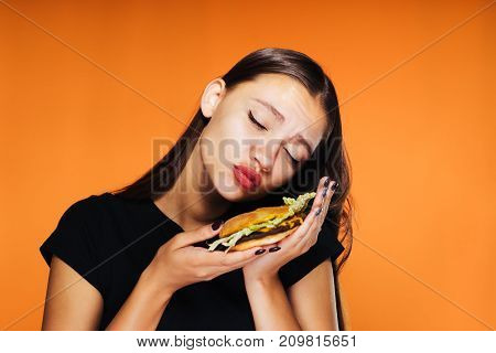 the girl is carefully holding a burger on an orange background
