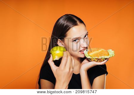 the girl angrily eats her burger holding an apple in her other hand