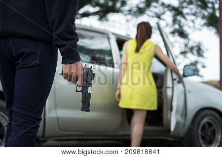 Bandit man with masked robber holding handgun weapon gangster to hijack hostage woman driver car shocked and dangerous on street violence concept