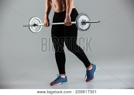 Cropped image of a muscular adult sportswoman standing with a barbell isolated over gray background
