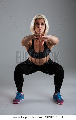 Portrait of a muscular adult sportswoman doing squats isolated over gray background
