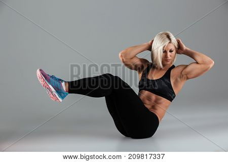 Portrait of a confident muscular adult sportswoman doing abs exercises isolated over gray background
