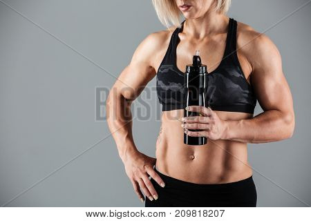Cropped image of a muscular adult woman holding a water bottle while standing and resting isolated over gray background