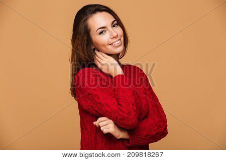 Image of cheerful caucasian lady dressed in sweater standing isolated. Looking camera.