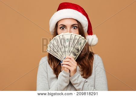 Photo of caucasian shocked lady wearing christmas hat standing isolated holding money. Looking camera.