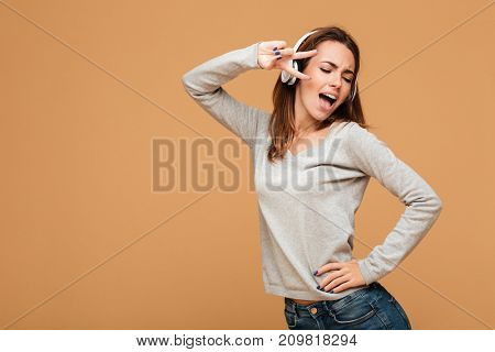 Image of emotional caucasian lady dancing isolated while singing and listening music. Looking aside.