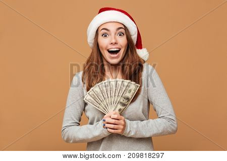 Photo of excited shocked caucasian lady wearing christmas hat standing isolated holding money. Looking camera.