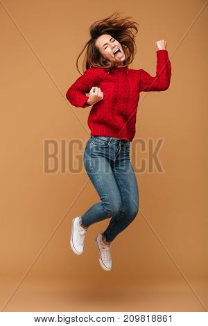 Photo of screaming caucasian woman dressed in sweater jumping isolated make winner gesture.