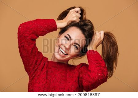 Picture of funny caucasian woman dressed in sweater standing isolated. Looking camera.