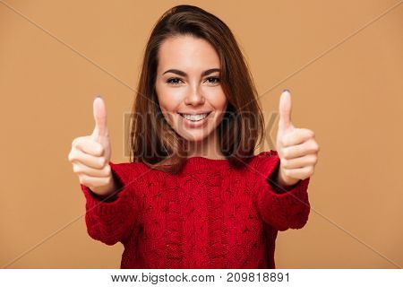 Image of cheerful caucasian lady with thumbs up dressed in sweater standing isolated. Looking camera.