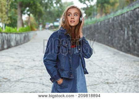 Portrait of a young pretty teenage girl listening to music with headphones while standing outdoors