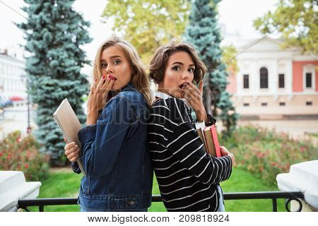 Two surprised young teenage girls with books covering their mouth while standing back to back outdoors on a city street
