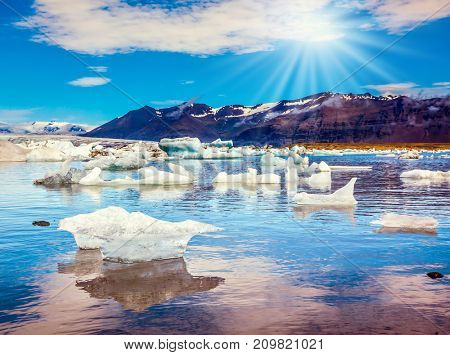 The concept of extreme northern tourism. Ice floes are reflected in the smooth water surface lake. Cool northern sun illuminates the Ice Lagoon