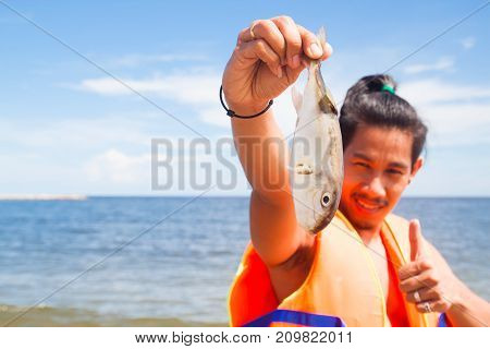 Asian man in life jacket holding died fish from the sea