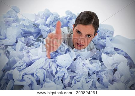 Conceptual image of woman in heap of crumple paper asking for help against grey background