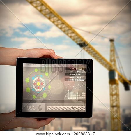 Close-up of hands holding digital tablet against 3d image of yellow crane