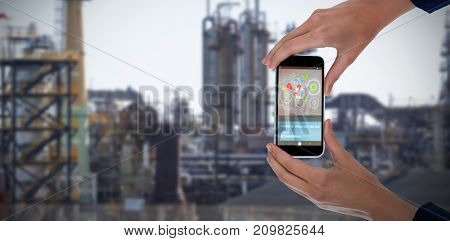 Cropped hands of businesswoman holding 3D mobile phone against image of factory