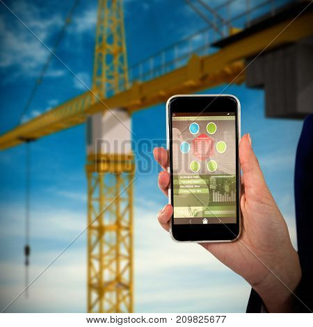Mid section of businesswoman holding mobile phone against low angle 3d image of yellow crane
