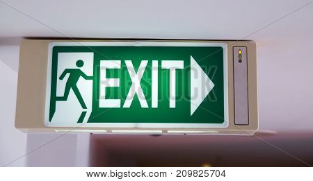 green emergency exit sign in public building (evacuation exit)