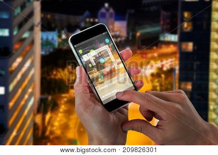 Close-up of cropped hands holding 3D mobile phone against illuminated road amidst building at night