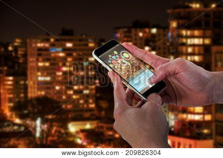 Close-up of man holding 3D smart phone against illuminated towers in city
