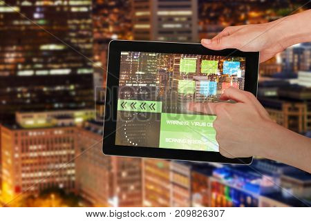 Hands touching digital 3D tablet against white background against illuminated building in city at night