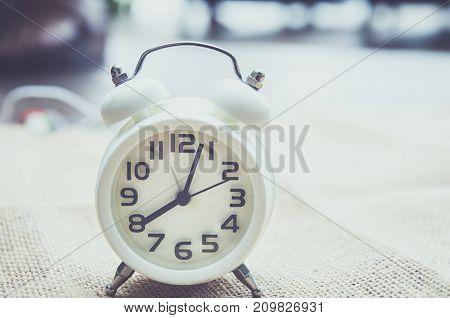 Retro alarm clock on a table. Photo in retro color image style
