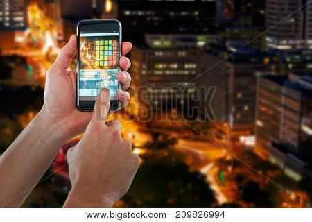 Cropped hand using 3D mobile phone against illuminated roads by buildings in city