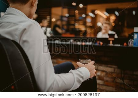man is holding a glass of whiskey in the barber's chair in barbershop