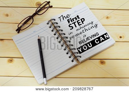 Phrase THE FIRST STEP IN ACHIEVING SOMETHING IS BELIEVING YOU CAN written on one page of a notebook. Inspirational and motivational.