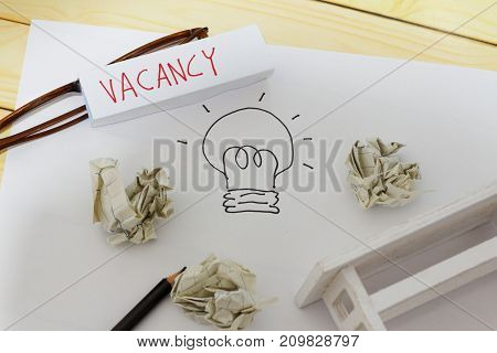 Vacancy and employment concept. White paper with drawing of a light bulb crumpled papers glasses pencil mini toy table and word VACANCY written on a small piece of paper.