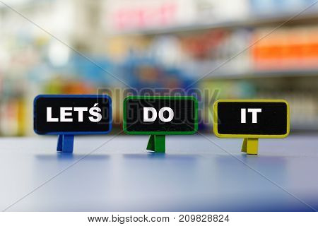 Motivational and inspirational words LET'S DO IT with colourful blurred background.