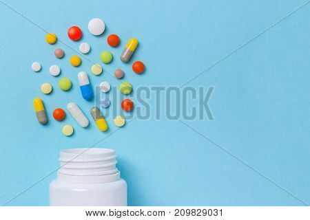 Assorted pharmaceutical medicine pills tablets and capsules and bottle on blue background. Copy space for text