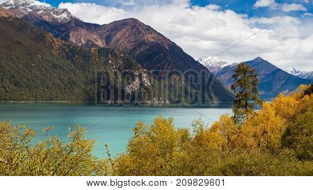 A turquoise high mountain lake surrounded by autumn trees. East Tibet, China.