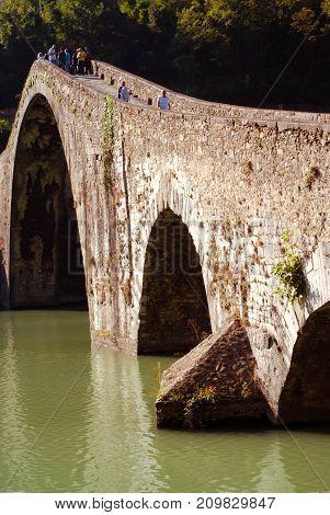 people walk on Maddalena bridge aka Devil bridge in tuscany Italy