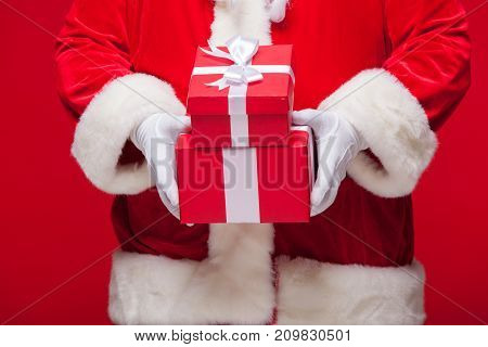 christmas Photo of Santa Claus gloved hand with red giftbox.