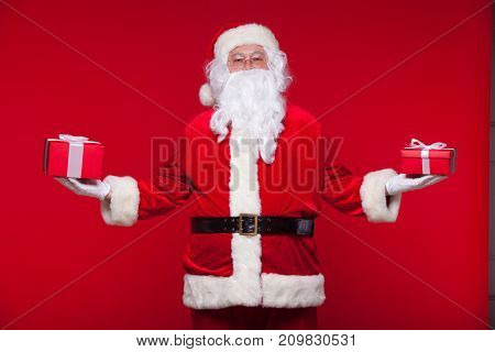 Christmas. Photo Santa Claus giving xmas present and looking at camera, on a red background.