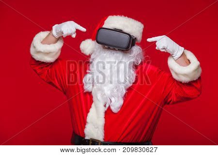 Santa Claus wearing virtual reality goggles, on a red background. Christmas.