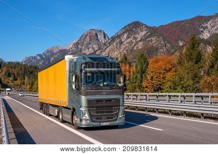 TYROL AUSTRIA - October 14 2017: A truck with a yellow van on a high-speed mountain road. In the background there are mountains and trees with red and yellow leaves.